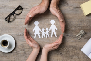paper cutout family protected by cupped hands
